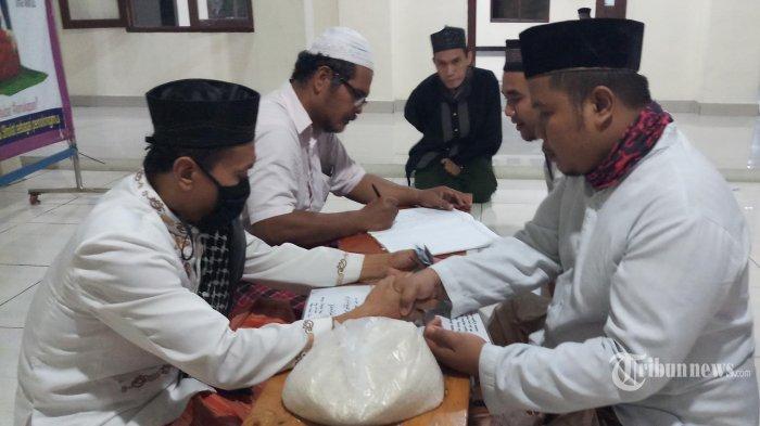 ZAKAT FITRAH - Warga sedang menunaikan zakat fitrah kepada panitia zakat Musola Miftahul Jannah, Desa Mekarsari, Kecamatan Rajeg, Kabupaten Tangerang, Senin (18/5/2020).