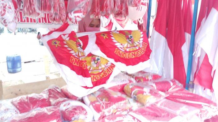 PENJUAL BENDERA - Itawati (35) penjual bendera merah putih dan umbul-mbul musiman sedang menggelar dagangannya di kawasan Tamansari, Jakarta Barat, Senin (20/7/2020). Beragam jenis bendera merah putih dengan berbagai ukuran berikut kelengkapannya termasuk lampion, balon hias, umbul-umbul, sticker hingga tiang bendera ditawarkannya dengan harga antara Rp 5 ribu hingga Rp 600 ribu/unit. Perayaan HUT RI ke 75 di masa pandemi yang akan diselenggarakan secara sederhana sangat mempengaruhi omset para penjual bendera, karena banyak masyarakat yang mengalami kesulitan ekonomi akibat terdampak Covid-19. WARTA KOTA/NUR ICHSAN
