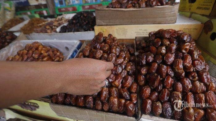 Pedagang sedang menata kurma yang berjualan di sekitar Jalan KH Mas Mansyur, Tanah Abang, Jakarta, Selasa (21/4/2020). Pandemi Covid-19 yang melanda Jakarta membuat lesu penjualan kurma, keuntungan pedagang menurun hingga 80 persen lebih padahal pada tahun sebelumnya menjelang Ramadhan biasanya ramai pembeli. TRIBUNNEWS/HERUDIN
