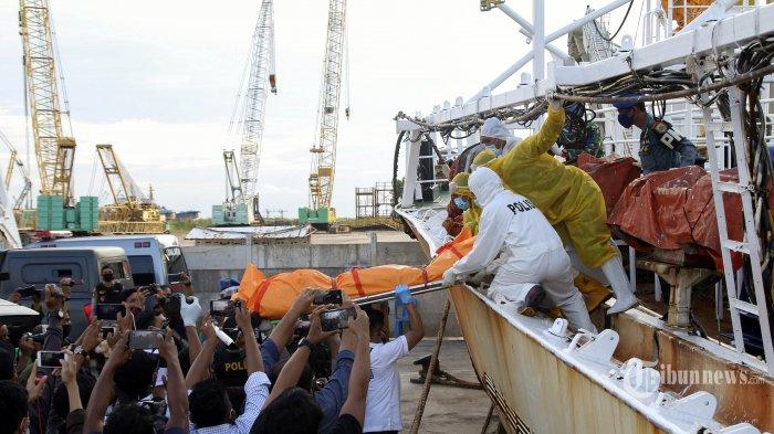 Anggota TNI AL dan Polisi menurunkan jenazah Warga Negara Indonesia (WNI), Hasan Afriadi yang menjadi anak buah kapal (ABK) Luang Huang Yuan Yu 118 di Dermaga Lanal Batam, Rabu (8/7/2020). Tim gabungan yang terdiri dari TNI AL, Polisi, Bakamla, KPLP dan Bea Cukai ini mengamankan dua kapal ikan berbendera China dengan nama lambung Luang Huang Yuan Yu 117 dan Luang Huang Yuan Yu 118 terkait tindak penganiyaan yang mengakibatkan satu ABK asal Indonesia meninggal dunia. TRIBUN BATAM/ARGIANTO DA NUGROHO
