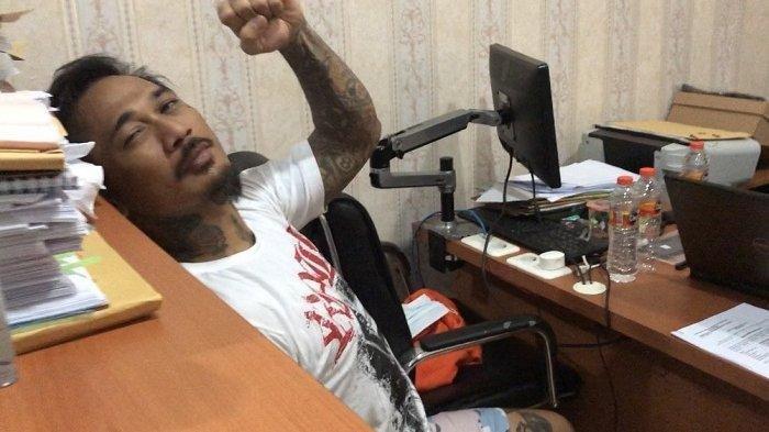 Jerinx mengepalkan tangan kiri sebelum menjalani pemeriksaan di Polda Bali. Jerinx diperiksa terkait kasus yang menjeratnya, Selasa (18/8/2020).