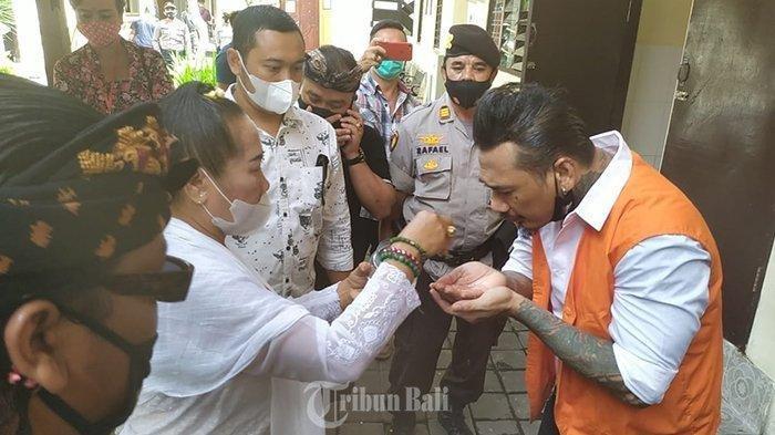 I Gede Ary Astina alias Jerinx diperciki air suci (tirta) oleh Ida Rsi Bujangga yang merupakan ibunda Jerinx jelang sidang di kasus dugaan ujaran kebencian 'IDI Kacung WHO' di Pengadilan Negeri Denpasar, Selasa (10/11/2020).