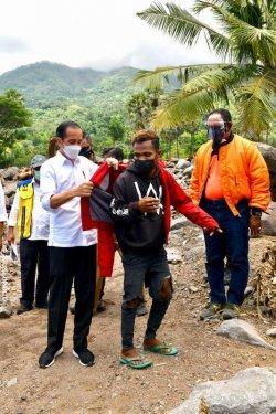 Presiden Joko Widodo mencopot jaketnya lalu mengenakannya kepada Fransiskus Ade Uran Atawalo, salah satu warga desa Tapolangun, Kab Lembata yang juga menjadi korban Banjir Bandang Lembata NTT (9/4/2021)