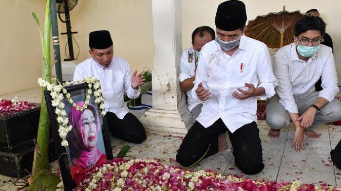 Presiden Joko Widodo (Jokowi) duduk disamping pusara ibundanya Sujiatmi Notomihardjo di pemakaman Keluarga Mundu, Selokaton, Gondangrejo, Karanganyar, Jawa Tengah, Kamis (26/3/2020)