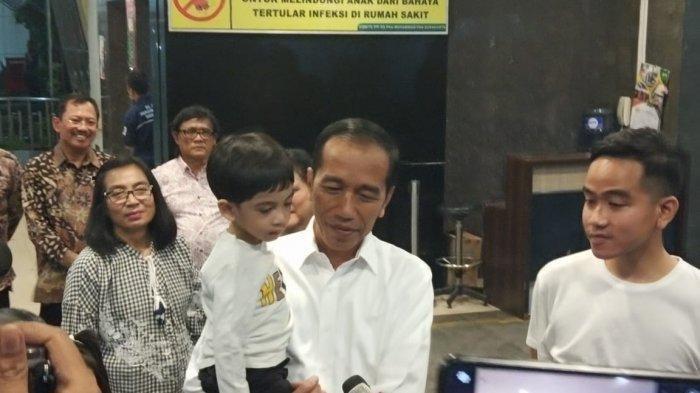 Jokowi menggendong Jan Ethes Srinarendra dan Gibran Rakabuming Raka di depan Rumah Sakit PKU Muhammadiyah Solo, Jumat (15/11/2019) pukul 21.10 WIB. TRIBUNSOLO.COM/AGIL TRI