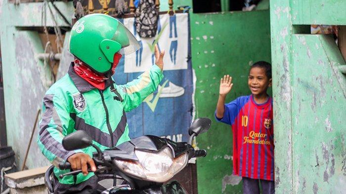 Joni Sius Tse, mitra pengemudi GrabBike yang berpamitan kepada anaknya sebelum bekerja.