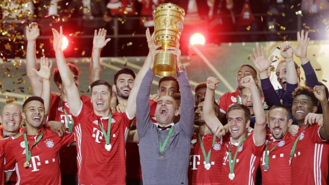 Pelatih Bayern Muenchen, Josep Guardiola mengangkat trofi Piala Jerman.