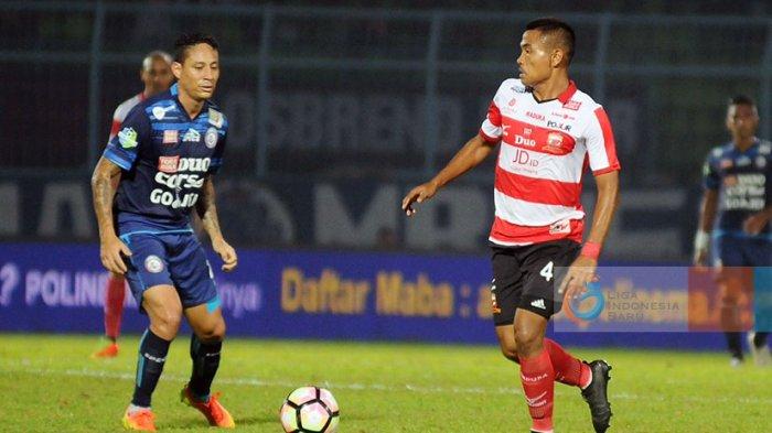 Pemain Madura United, Asep Berlian (putih-merah) bersiap menendang bola dibayangi penyerang Arema, Juan Pablo Pino.