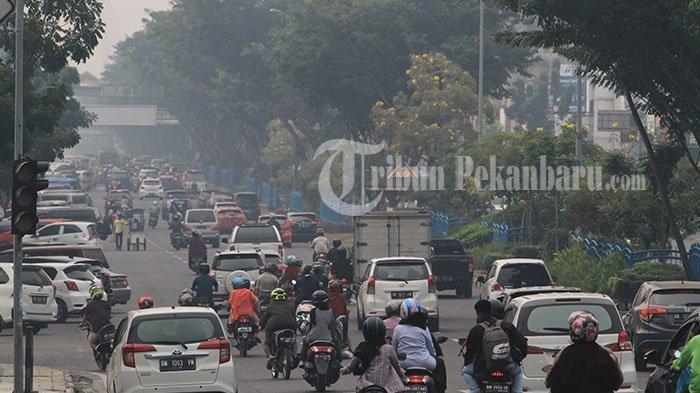 Kabut asap menyelimuti kawasan Jalan Sudirman Pekanbaru, Minggu (25/8/2018). TRIBUN PEKANBARU/THEO RIZKY