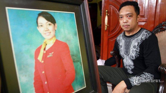 Irfan kakak pramugari, bersama foto adiknya Isti Yudha Prastika yang sebagai ekstra kru duduk di seat 20 C  dalam pesawat Sriwijaya Air Sj 182 yang jatuh  di kepulauan Seribu, Kompleks Reni Jaya lama,  Jalan Sumatera, Reni Jaya, Pamulang, Tangerang Selatan, Minggu (10/1/2021). (WARTAKOTA/Henry Lopulalan)