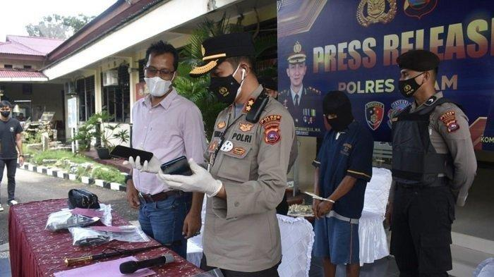 Kapolres Agam AKBP Dwi Nur Setiawan saat memegang barang bukti yang ikut disita, Jumat (10/9/2021).