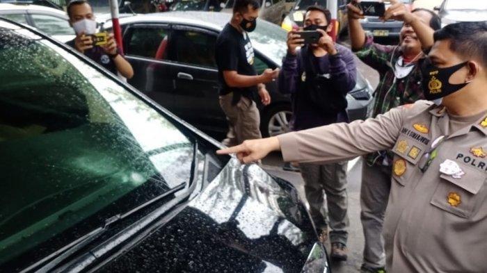 Kapolresta Solo Kombes Pol Ade Safri Simanjuntak menunjukan bagian Mobil Toyota Alphard yang bolong karena tertembak di Jalan Monginsidi Solo, Rabu (2/11/2020).