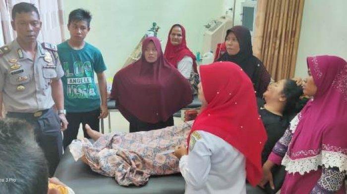 Kapolsek Babahrot, Iptu Rizal Firmansyah melihat Husnita (35), warga Dusun Alue Trieng Gadeng, Desa Kayee Aceh, Kecamatan lembah Sabil, Kabupaten Abdya, ketika ditangani para medis di Puskesmas Babahrot, Senin (19/8/2019) siang. Wanita dalam kondisi trauma dan tidak bisa diajak bicara itu sebelumnya diantar sopir labi-labi, dan diduga kuat korban hipnotis di Pasar Manggeng. SERAMBINEWS.COM/ZAINUN YUSUF