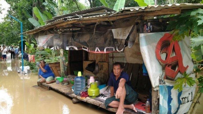 Kardi (70) saat terduduk memandangi banjir dari atas gubuknya ditemani sang istri di Desa Dukuh, Kecamatan/Kabupaten Indramayu, Kamis (5/3/2020).