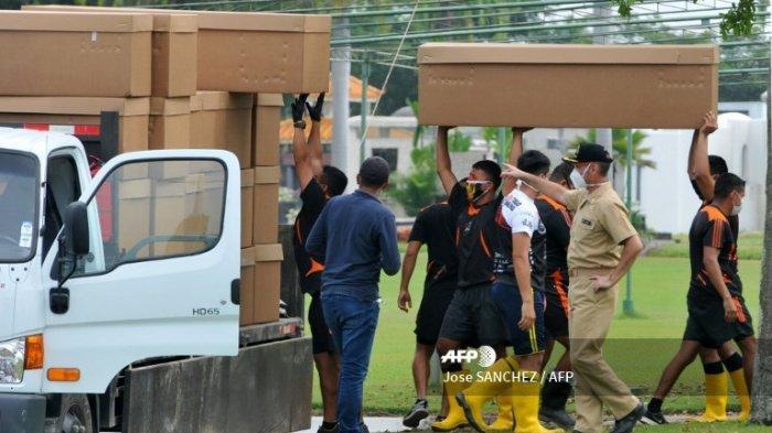 Tentara mengangkut kotak-kotak kardus yang digunakan sebagai peti mati di pemakaman Paque de la Paz di Guayaquil, Ekuador, pada 9 April 2020 karena meningkatnya jumlah virus coronavirus COVID-19 di kota itu yang menyebabkan kekurangan peti mati.