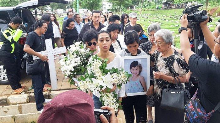 Karen Pooroe pegang foto almarhumah anaknya Zefania Carina di TPU Tanah Kusir, Minggu (9/2/2020).