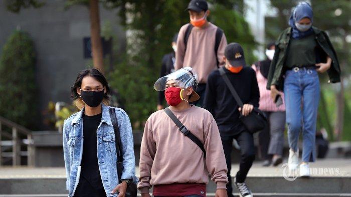 Pekerja saat mengenakan masker saat akan pulang menggunakan kendaraan umum di kawasan Sudirman, Jakarta Pusat, Selasa (21/7/2020).