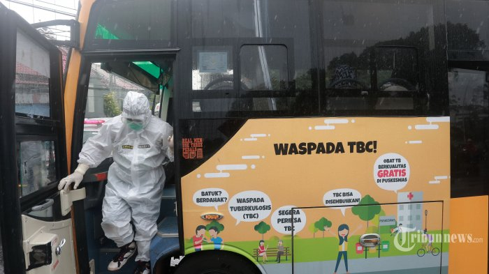 Petugas kesehatan bersiap membawa pasien Covid-19 menggunakan Bus Sekolah menuju Rumah Sakit Darurat Wisma Atlet Kemayoran dari Puskesmas Jatinegara, Jakarta Timur, Selasa (26/1/2021). Berdasarkan data Satuan Tugas Penanganan Covid-19 pada Selasa (26/1/2021) pukul 12.00 WIB, total ada 1.012.350 kasus Covid-19 di Tanah Air setelah ada penambahan 13.094 kasus baru. Tribunnews/Irwan Rismawan