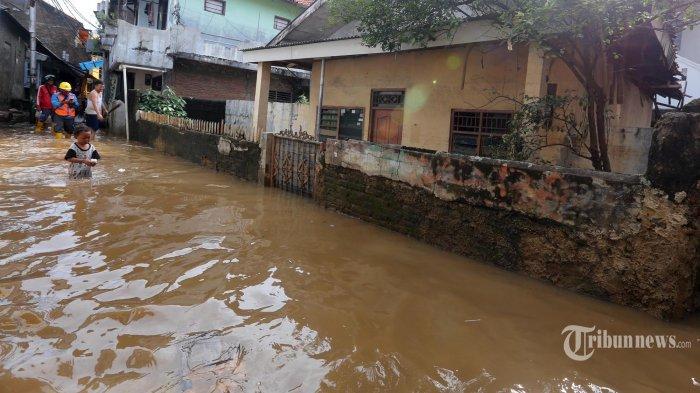 Warga beraktivitas di lingkungan RW 07 Kelurahan Kampung Melayu, Jakarta Timur, yang terendam banjir, Sabtu (8/2/2020). Kawasan permukiman ini terendam banjir akibat intensitas hujan yang tinggi dan luapan Sungai Ciliwung.  Warta Kota/Alex Suban