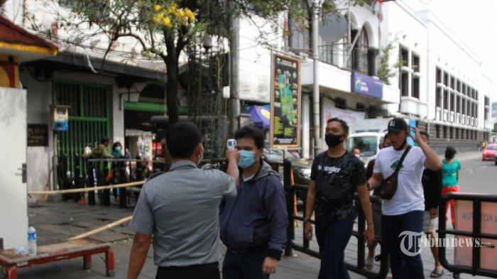 Warga mengisi libur panjang dengan mengunjungi kawasan Kota Tua di Jakarta Barat, Kamis (29/10). Mesmasuki PSBB transisi kawasan kota tua di buka kembali untuk wisatawan yang hendak berlibur dikawasan bangunan tua tersebut. Pembukaan untuk warga berwisata hanya lorong atau jalan. Sementara alun-alun musium Fatahillah belum dibuka. Petugas menjaga  dan melarang warga yang hendak memasuki lapangan luas, memasuki komplek kota tua tersebut setiap pengujung harus cek suhu badan, pakai masker dan wajib cuci tangan. Untuk anak- anak usia dibawah 10 tahun dilarang masuk. (Warta Kota/Henry Lopulalan)