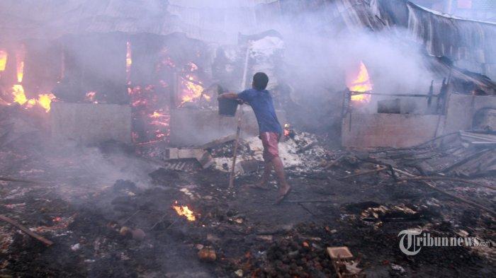 Petugas pemadam kebakaran bersama warga beusaha memadamkan kebakaran hebat yang terjadi di Jalan Sabeni Raya No 12 RT 01/RW 12, Pasar kambing, Tanah Abang, Jakarta Pusat, Kamis (8/4/2021). Tim pemadam kebakaran sejauh ini telah mengerahkan 15 unit pemadam kebakaran dan 75 personel menguasi si jago merah yang melahap pasar dan rumah warga.  (Warta Kota/Henry Lopulalan)