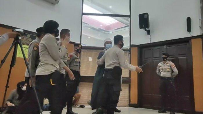 Polisi giring salah seorang keluarga Gus Nur keluar ruang sidang, di Pengadilan Negeri Jakarta Selatan, Selasa (23/2/2021).