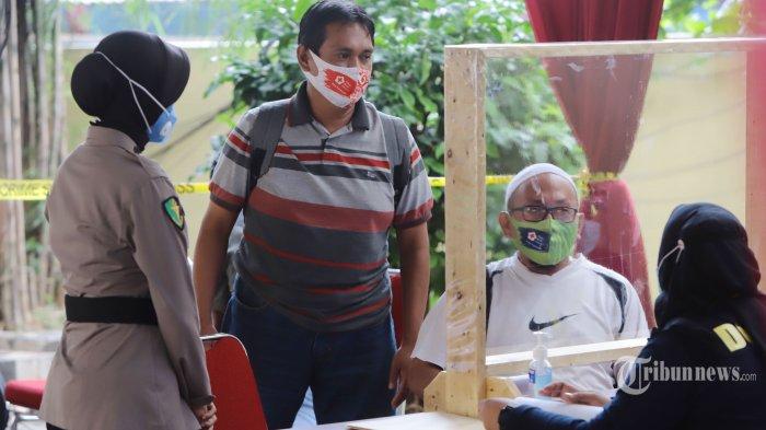 Keluarga korban jatuhnya pesawat Sriwijaya Air SJ 182 mendatangi Posko Antemortem-DVI RS Polri Sukanto, Jakarta, Selasa (12/1/2021). Keluarga korban mulai berdatangan ke posko ante mortem untuk memberikan Informasi data primer dan sekunder yang diperlukan tim forensik RS Polri. TRIBUNNEWS/HERUDIN