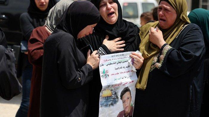 Kerabat menghibur Ruba al-Tamimi saat dia berduka atas putranya Muhammad selama prosesi pemakamannya di Deir Nizam, barat kota Ramallah di Tepi Barat yang diduduki, pada 24 Juli 2021, setelah kematiannya karena luka tembak yang diderita sehari sebelumnya selama bentrokan dengan tentara Israel. Al-Tamimi tewas setelah ditembak dalam bentrokan dengan tentara Israel pada protes atas permukiman ilegal di Tepi Barat yang diduduki, kata pihak berwenang Palestina. Remaja berusia tujuh belas tahun yang menderita luka tembak, kemudian meninggal di rumah sakit, kata kementerian kesehatan Palestina, sehari setelah kekerasan di desa Beita, Palestina.