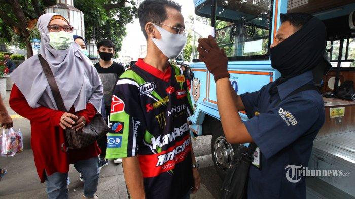 Petugas memeriksa suhu tubuh setiap wisatawan saat naik bus Bandros (Bandung Tour On Bus) di Halte Alun-alun Bandung, Jalan Dalem Kaum, Kota Bandung, Jawa Barat, Minggu (21/6/2020). Sebanyak 12 unit bus Bandros sudah kembali beroperasi melayani wisatawan berkeliling Kota Bandung dengan menerapkan protokol kesehatan guna mencegah penularan virus corona (Covid-19), yakni dengan mewajibkan setiap wisatawan memakai masker selama di dalam bus, diperiksa suhu tubuh sebelum naik bus, dan jumlah wisatawan di dalam bus dibatasi maksimal 50 persen dengan memberlakukan physical distancing atau jaga jarak aman dengan memberi tanda silang merah di kursi yang tidak boleh diduduki. Tribun Jabar/Gani Kurniawan
