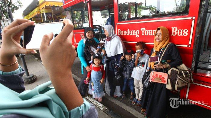 Sejumlah wisatawan yang sedang melintas menyempatkan foto bersama di samping bus Bandros (Bandung Tour On Bus) di Halte Alun-alun Bandung, Jalan Dalem Kaum, Kota Bandung, Jawa Barat, Minggu (21/6/2020). Sebanyak 12 unit bus Bandros sudah kembali beroperasi melayani wisatawan berkeliling Kota Bandung dengan menerapkan protokol kesehatan guna mencegah penularan virus corona (Covid-19), yakni dengan mewajibkan setiap wisatawan memakai masker selama di dalam bus, diperiksa suhu tubuh sebelum naik bus, dan jumlah wisatawan di dalam bus dibatasi maksimal 50 persen dengan memberlakukan physical distancing atau jaga jarak aman dengan memberi tanda silang merah di kursi yang tidak boleh diduduki. Tribun Jabar/Gani Kurniawan