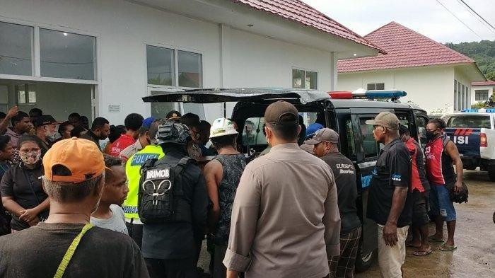 Kepolisian dan pihak keluarga membawa jenazah FR ke mobil ambulans. FR tewas dalann insiden dua kelompok warga saling serang di Manokwari, Minggu (19/4/2021).