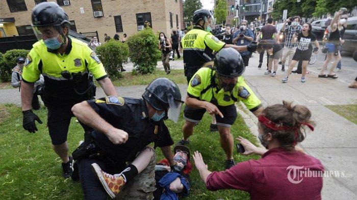 Sejumlah Polisi menahan pengunjuk rasa dalam aksi demonstrasi Black Lives Matter di luar Kantor Polisi Distrik Empat, Boston, Massachusetts, Sabtu (29/5/2020). Amerika Serikat dilanda kerusuhan hebat, pasca meninggalnya George Floyd akibat kehabisan nafas, setelah lehernya ditindih seorang petugas Polisi Minneapolis dalam sebuah penangkapan. AFP/JOSEPH PREZIOSO