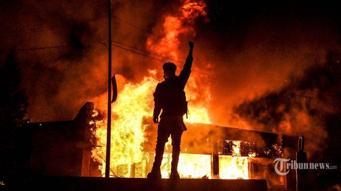 ILUSTRASI - Pengunjukrasa berdiri di depan gedung yang terbakar dalam aksi demonstrasi di Minneapolis, Minnesota, Jumat (29/5/2020). Amerika Serikat dilanda kerusuhan hebat, pasca meninggalnya George Floyd akibat kehabisan nafas, setelah lehernya ditindih seorang petugas Polisi Minneapolis dalam sebuah penangkapan. AFP/CHANDAN KHANNA