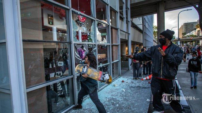 Seorang pengunjukrasa memukulkan skateboardnya ke jendela sebuah restoran di pusat kota Los Angeles, Sabtu (30/5/2020). Amerika Serikat dilanda kerusuhan hebat, pasca meninggalnya George Floyd akibat kehabisan nafas, setelah lehernya ditindih seorang petugas Polisi Minneapolis dalam sebuah penangkapan. AFP/APU GOMES