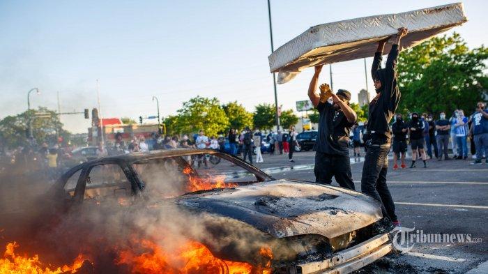 Pengunjukrasa melemparkan matras ke mobil yang terbakar di dekat Kantor Polisi di Minneapolis, Minnesota, Kamis (28/5/2020). Amerika Serikat dilanda kerusuhan hebat, pasca meninggalnya George Floyd akibat kehabisan nafas, setelah lehernya ditindih seorang petugas Polisi Minneapolis dalam sebuah penangkapan. AFP/KEREM YUCEL