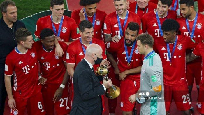 Presiden FIFA Gianni Infantino (tengah) mempersembahkan trofi kepada penjaga gawang Bayern Munich Jerman Manuel Neuer menyusul pertandingan final Piala Dunia Antarklub FIFA antara Bayern Munich vs UANL Tigres Meksiko di Education City Stadium di kota Ar-Rayyan di Qatar pada 11 Februari , 2021. Karim JAAFAR / AFP