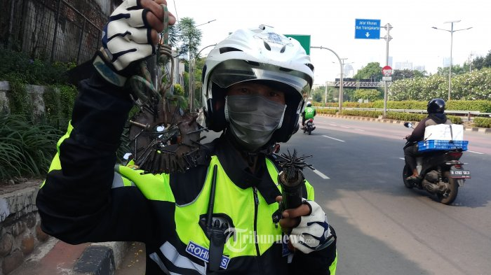 SAPU RANJAU.PAKU - Abdul Rohim dari Komunitas Sapu Ranjau ( Saber) sedang melakukan penyapuan ranjau paku yang banyak berserakan di Jalan Gatot Subroto, Jakarta, Pusat, Minggu (14/6/2020). Ranjau paku yang disebar orang tak bertanggung jawab ini membahayakan motor dan mobil pengguna jalan karena tak sedikit yang mengalami kecelakaan ban kempes terkena paku ranjau.