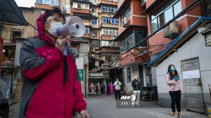 Foto yang diambil pada 18 Maret 2020 menunjukkan warga berbaris untuk mengambil daging babi yang dikirim ke kompleks karantina mereka di Wuhan, Provinsi Hubei, China. Pada Kamis (19/3/2020), China melaporkan tidak ada kasus baru dalam virus corona untuk pertama kalinya sejak wabah ini muncul.