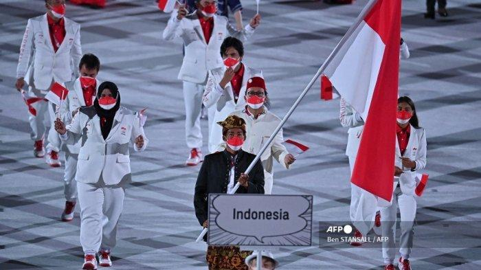 Pengibar bendera Indonesia Nurul Akmal dan delegasi berparade saat upacara pembukaan Olimpiade Tokyo 2020, di Stadion Olimpiade, di Tokyo, pada 23 Juli 2021.