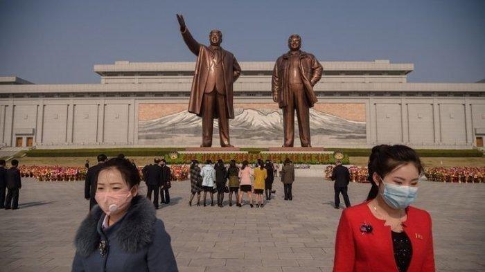 Orang-orang yang memakai topeng wajah pergi setelah meletakkan bunga di depan patung-patung pemimpin Korea Utara Kim Il Sung dan Kim Jong Il pada kesempatan ulang tahun ke-108 dari pemimpin Korea Utara Kim Il Sung, yang dikenal sebagai Day of the Sun, di Pyongyang pada 15 April 2020.