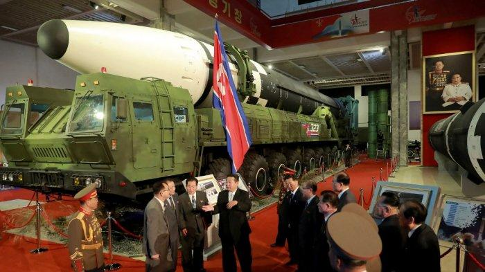 Gambar ini diambil pada 11 Oktober 2021 dan dirilis dari Kantor Berita Pusat Korea (KCNA) pada 12 Oktober menunjukkan pemimpin Korea Utara Kim Jong Un (tengah) berbicara di depan rudal balistik antarbenua (ICBM) yang ditampilkan selama pameran pengembangan pertahanan