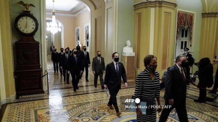 Panitera DPR Cheryl Johnson (kiri) bersama dengan Polisi Pengadilan DPR Tim Blodgett berjalan melalui koridor Ohio Clock Capitol saat mereka memimpin manajer pemakzulan Demokrat untuk menyampaikan artikel pemakzulan Donald Trump pada 25 Januari 2021 di Washington, DC.