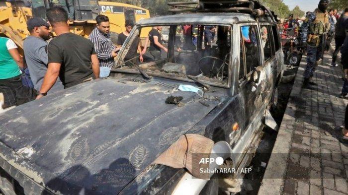 Orang-orang berkumpul di sekitar kendaraan yang hancur di lokasi ledakan di distrik Habibiya di pinggiran Kota Sadr, ibu kota Irak, Baghdad pada 15 April 2021. Setidaknya satu warga sipil tewas dalam ledakan di kubu Syiah yang padat penduduk di Kota Sadr di Baghdad timur, tentara Irak melaporkan, tanpa menentukan penyebab atau pelakunya.