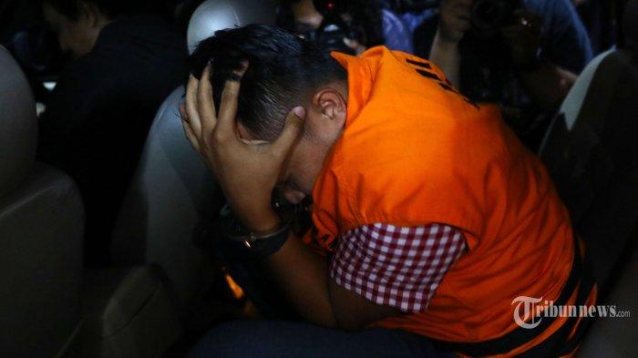 Direktur PT Navy Arsa Sejahtera Mujib Mustofa keluar menutupi wajahnya menggunakan rompi oranye usai menjalani pemeriksaan di gedung KPK, Jakarta, Rabu (25/9/2019) dini hari. KPK resmi menahan dua orang tersangka yakni Direktur Utama Perum Perikanan Indonesia Risyanto Suanda dan Direktur PT Navy Arsa Sejahtera Mujib Mustofa sebagai penyuap serta mengamankan 30ribu USD terkait dugaan suap kuota impor ikan tahun 2019.  TRIBUNNEWS/IRWAN RISMAWAN