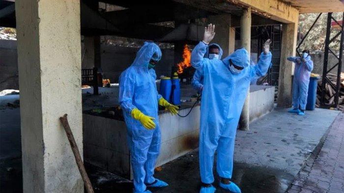 Petugas membersihkan diri dengan disinfektan usai melakukan kremasi mayat korban covid-19.