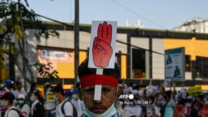 Seorang pengunjuk rasa memakai tanda dengan salam tiga jari selama demonstrasi menentang kudeta militer di Yangon pada 22 Februari 2021.