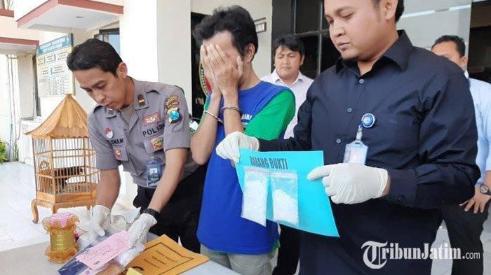 Moch Kholifa Ismail (39) kurir narkoba jaringan lapas hanya bisa menutupi wajahnya di Mapolrestabes Surabaya, Kamis (29/8/2019). SURYA.CO.ID/WILLY ABRAHAM