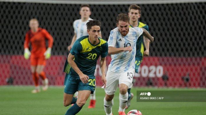 Lachlan Wales (tengah) dari Australia berlari dengan bola melewati gelandang Argentina Alexis Mac Allister selama pertandingan sepak bola putaran pertama grup C putra Olimpiade Tokyo 2020 antara Argentina dan Australia di Sapporo Dome di Sapporo pada 22 Juli 2021.