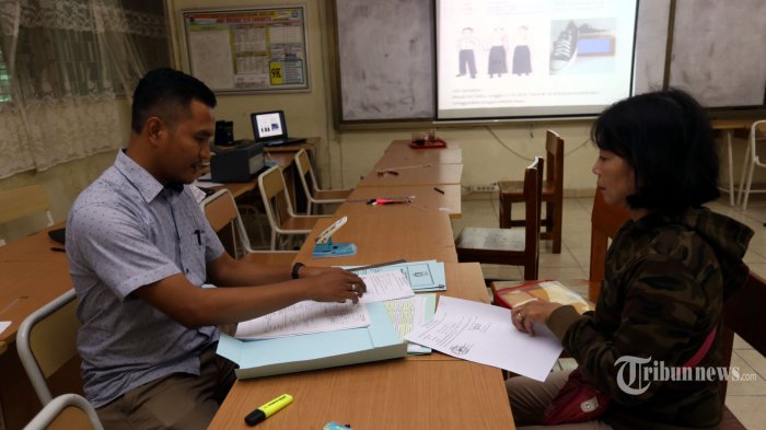 ILUSTRASI - Orang tua calon siswa Calon Peserta Didik Baru (CPDB) menyerahkan berkas lapor diri Jalur Afirmasi non Zonasi di SMP Negeri 216, Salemba, Jakarta Pusat, Senin (8/7/2019). Jadwal Lapor Diri CPDB untuk SMP hingga Selasa (9/7/2019). Warta Kota/Angga Bhagya Nugraha