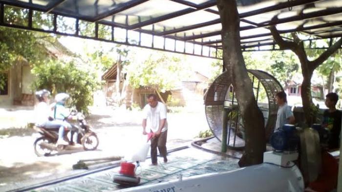 Ashari sedang membersihkan karpet masjid di usaha laundrynya, Padangan Piyungan Bantul, Senin (15/6/2015)